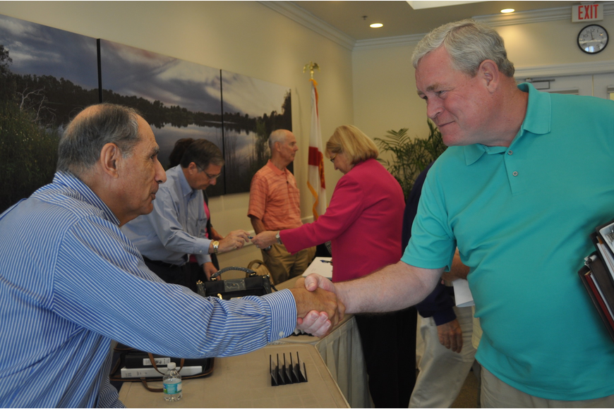 Robert Burstein, Lakewood Ranch CDD 6 supervisor, and David Emison, CDD 5 supervisor, congratulate each other after passing the cost-sharing agreement.