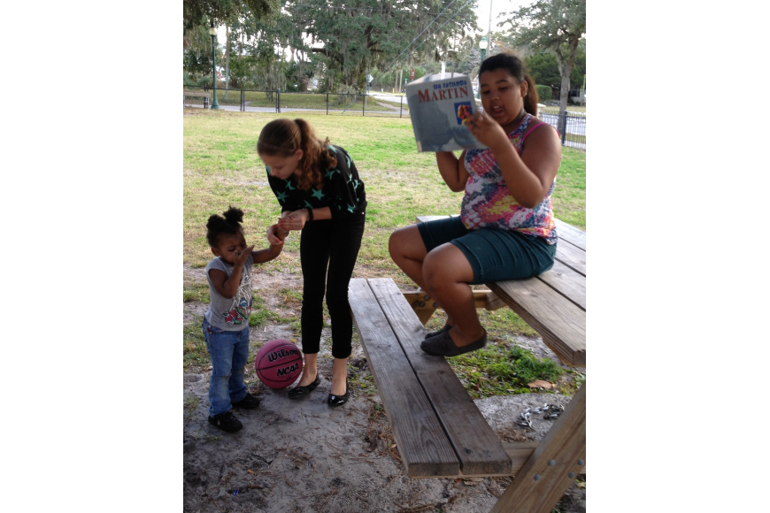Central-Cocoanut neighborkid Tatiana Johnson, 11, reads at Mary Dean Park as her sister Honestey, 2, and her cousin Camille Homer, 13, listen.