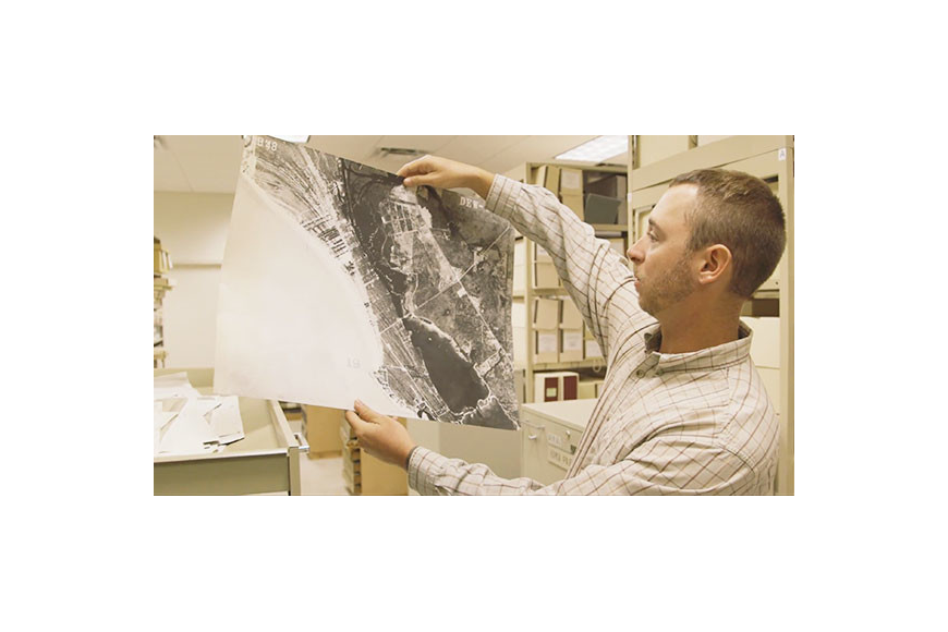 Sarasota County Archaeologist Ryan Murphy examines a historical aerial picture of the county's barrier islands.