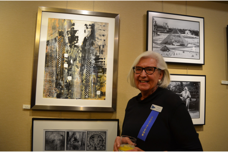 "Exhibitor Arlene Sjosten in front of her painting, ""City Life"""