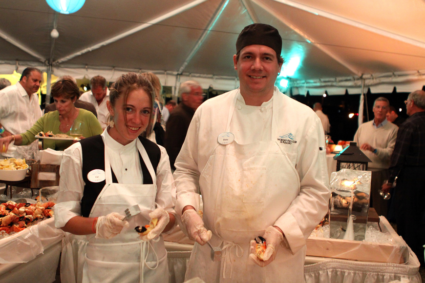 Kat Bouchard and Blake Halverson hold up some stone crab legs from their work table during the Wine & Stone Crab Celebration.