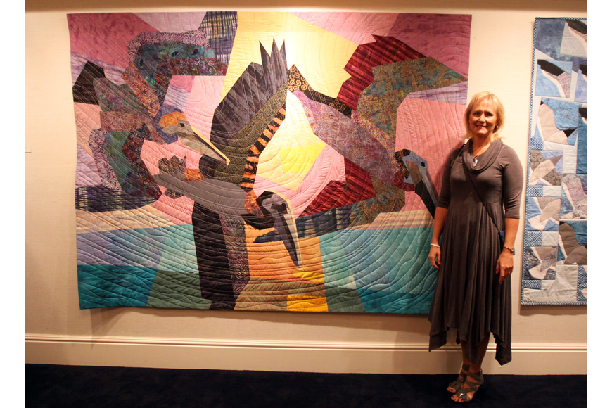 "Janine Ward poses next to her newest quilt ""Brown Pelicans"" during the art opening featuring her quilts at Bird Key Yacht Club."