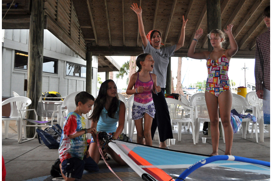 Farah Abid's, camp counselor, team celebrates after finishing putting their sail together before any of the other teams Friday, July 8 during the Island Style Water Sports Camp.