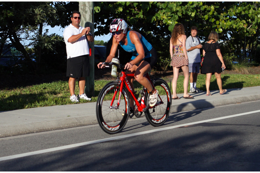 Kerry Simmons rides her bike down Beach road during the Siesta Key Triathlon Saturday, July 23 out at Siesta Key Public Beach.