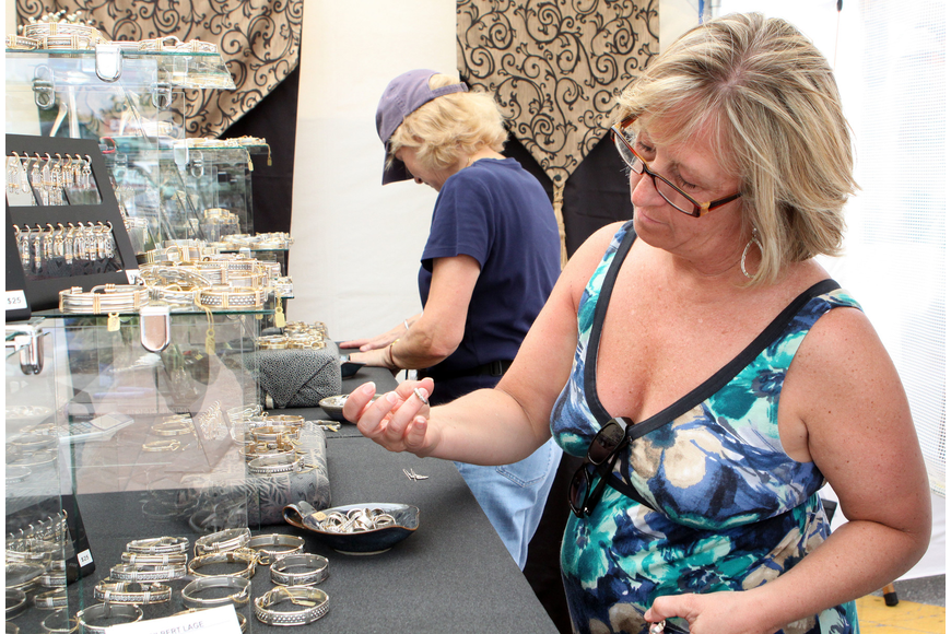Sue Kelly looks at some earrings and a ring from Gilbert Lage's booth at Siesta Fiesta.