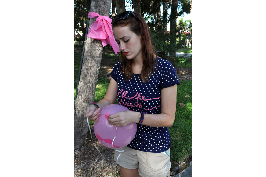 Katie Rees, 17, ties a ribbon onto a balloon.