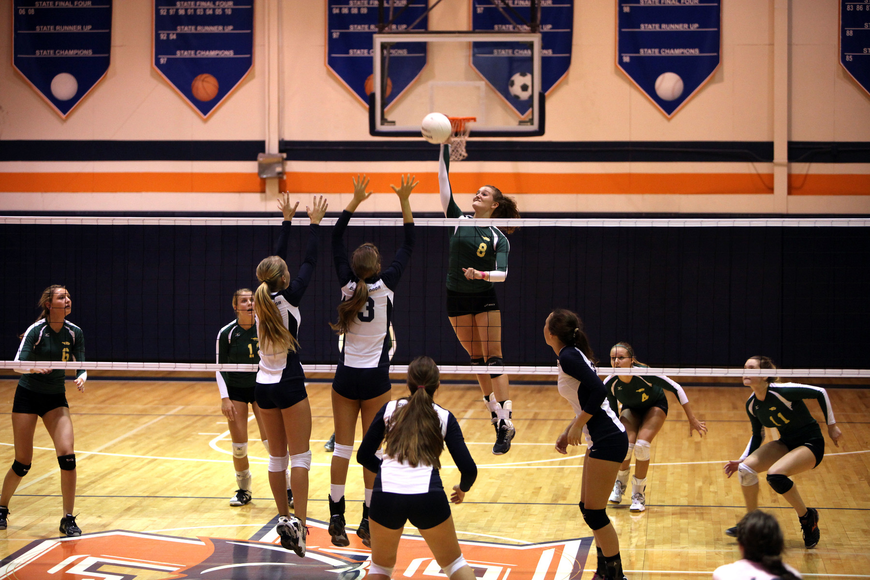 Tori Biach, No. 8, jumps up to spike the ball while Natalie Buffett, No. 4, and Gabriella Costa, No. 3, prepare to block Biach's shot.