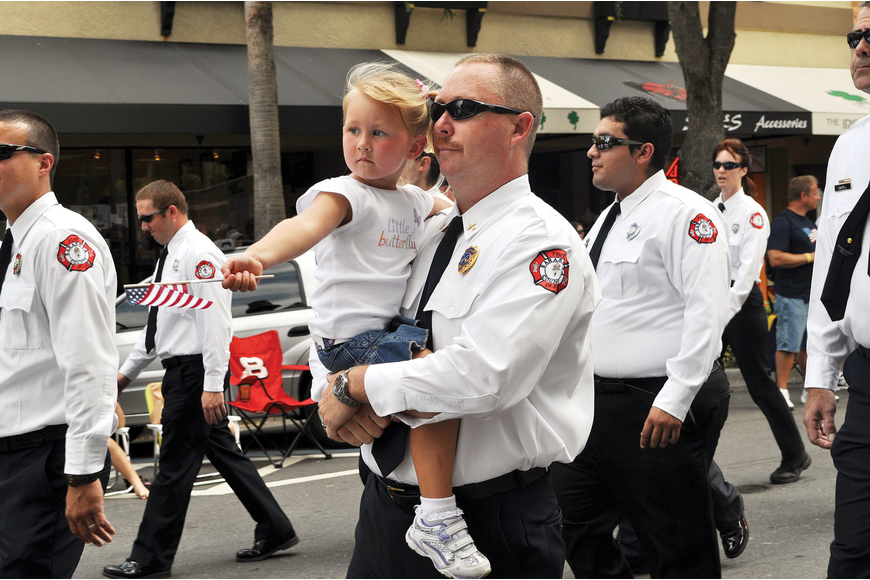 Glenn Snyder carries his daughter, Peyton, 3 for the annual Sarasota Memorial Day Parade, May 28, in downtown.