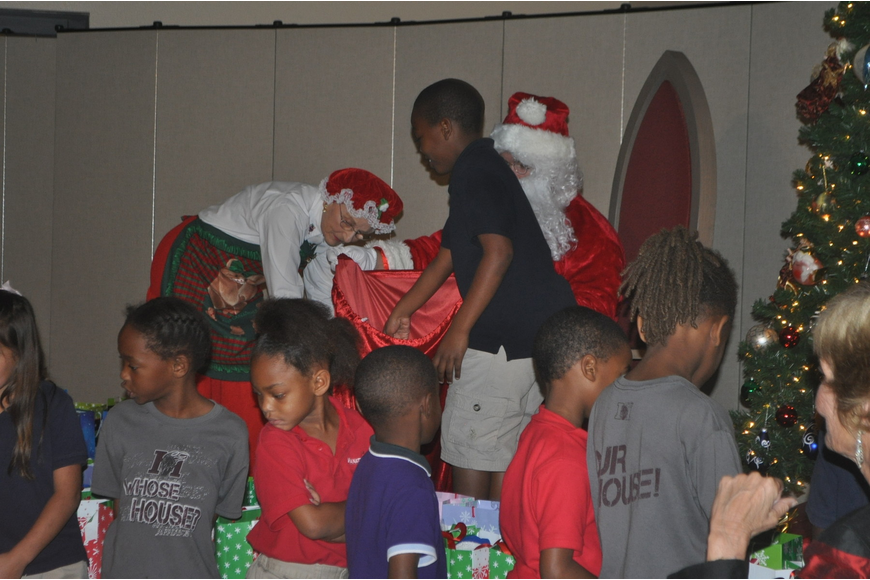 Ginny Dreher and Andy Rauch, dressed as Mr. and Mrs. Clause, distribute gifts to the children.