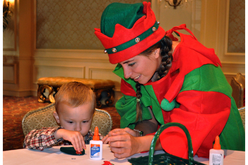 Elf Mandy helps Charlie Meyer, 2, make a candy cane mouse.