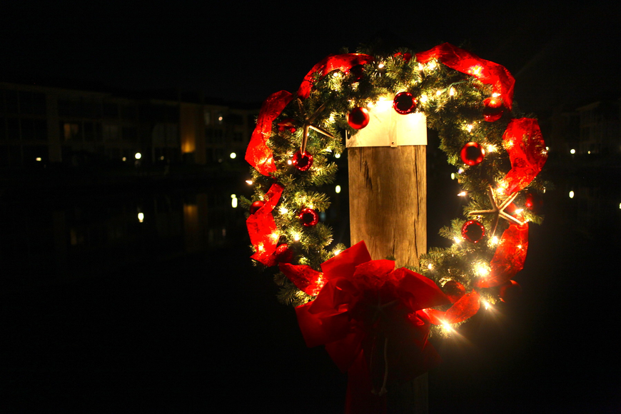 A festive wreath hangs from a dock.