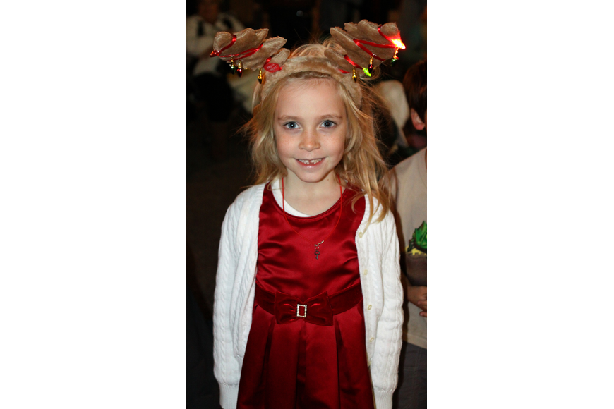 Abigail Koester wears reindeer ears that light up while she watched the parade on Main street on Saturday, Dec. 4.