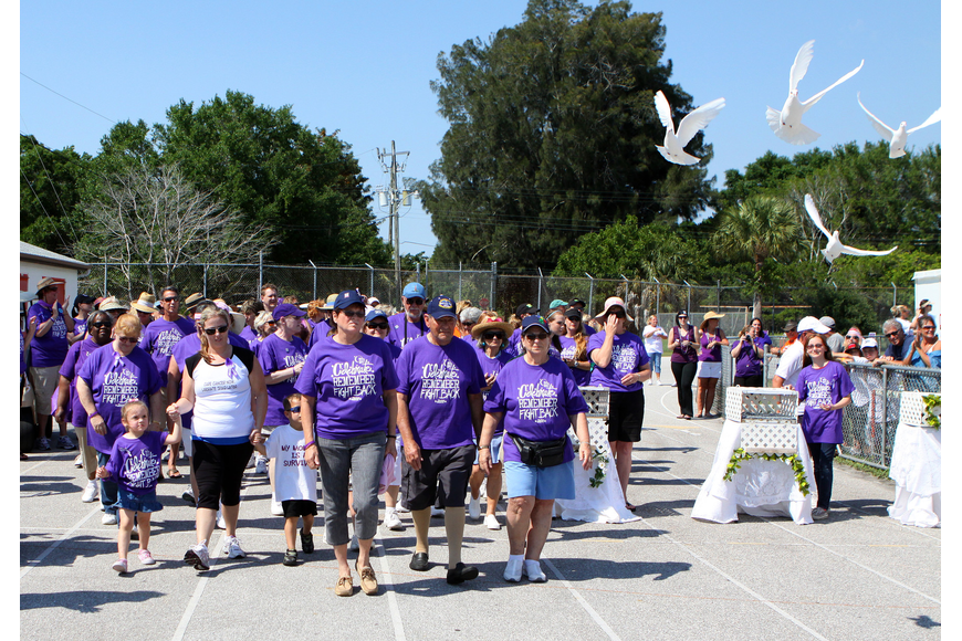 Survivors start their first lap while doves fly through the air on Saturday, April 9 at Sarasota High School.