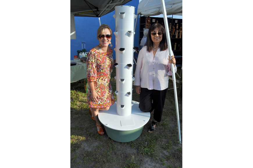 Caryn Patterson and Lillian Morales pose next to the Tower Garden.