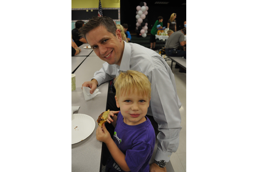 Caden Fluck was all smiles as he munched on doughnuts with his father, Rob.