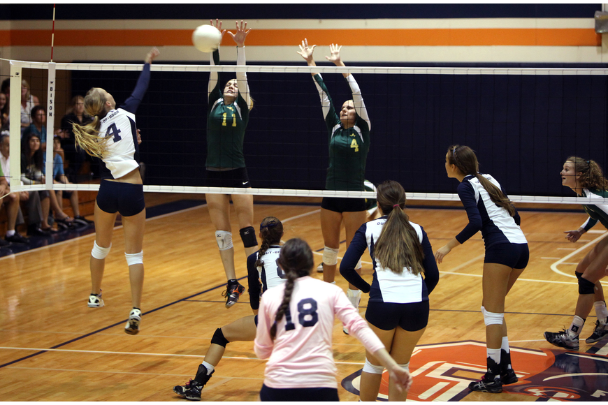Natalie Buffett, No. 4, spikes the ball towards Amanda Everhardus, No. 11, and Gabrielle Woodruff, No. 4.