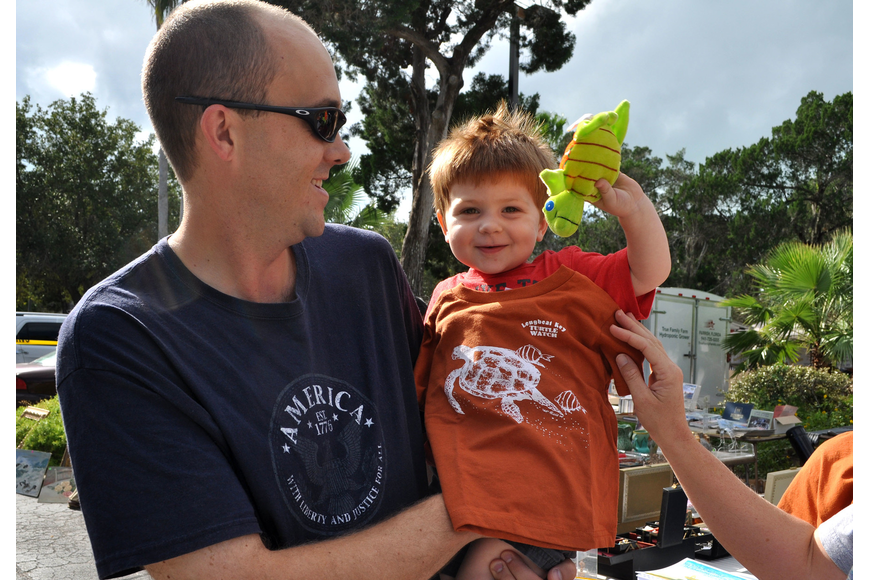 Cal Leggett holds his son, Alex, 2, as he gets sized for a Longboat Key Turtle Watch shirt and holds up a stuffed toy turtle Sunday, Oct. 28, during the Fall Festival at the Centre Shops.
