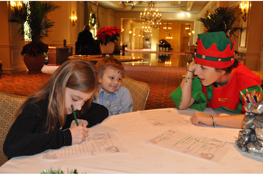 Marissa Govic, 8, works on writing her letter to Santa while Elf Morganna helps Jack Govic, 5, come up with things to put on his list to Santa.