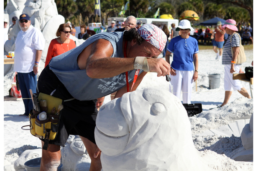 Steve Topazio does some careful detail work on his sand sculpture as beachgoers look on.