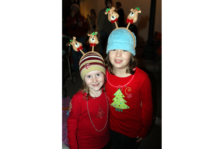 Faith and Desi Martin wear fun reindeer headbands and holiday shirts as they watch the parade.