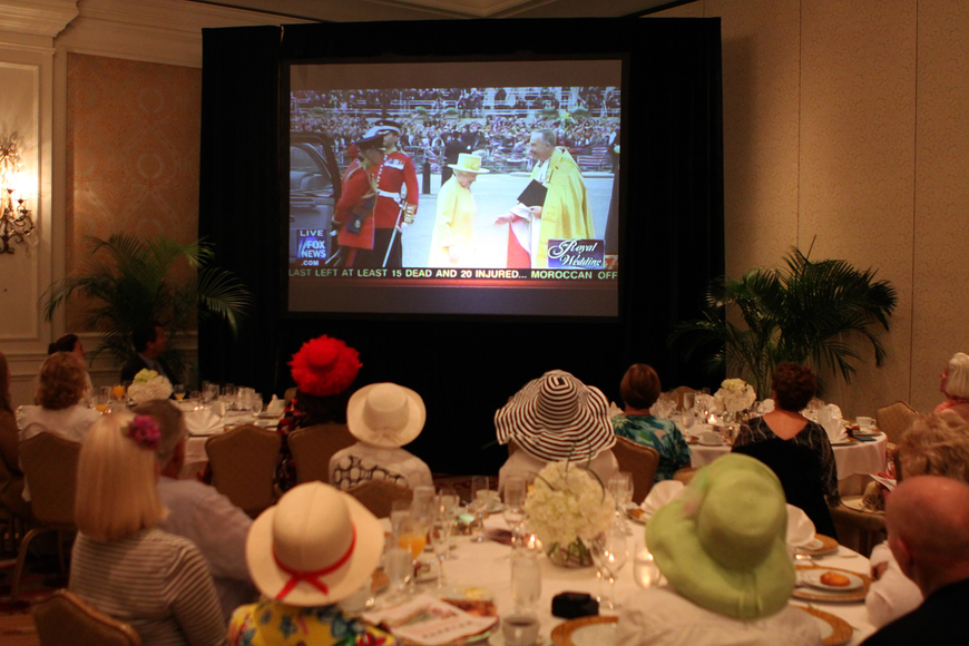 People watch Queen Elizabeth on TV and wore extravagant hats as part of the royal wedding party experience Friday, April 29 at the Ritz Carlton.