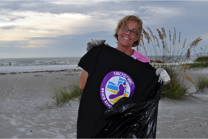 Jan Duffy shows off her free t-shirt for helping out with the Barefoot Wine Beach Cleanup Thursday, Sept. 8, at Ted Sperling Park.