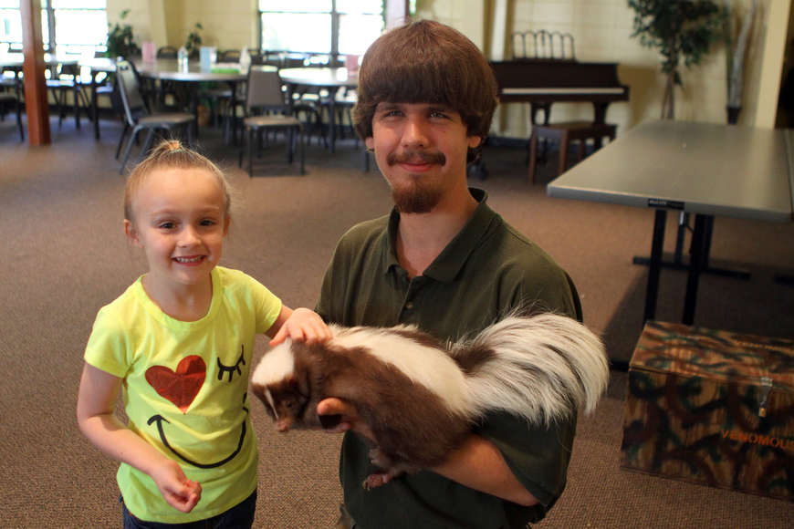 Violet Walsh poses with Jeremiah Nichol and Jungle Gardens' skunk, Mocha, Thursday, Jan. 12, inside the Parish Hall at St. Boniface. Walsh got a kiss on the hand from Mocha.