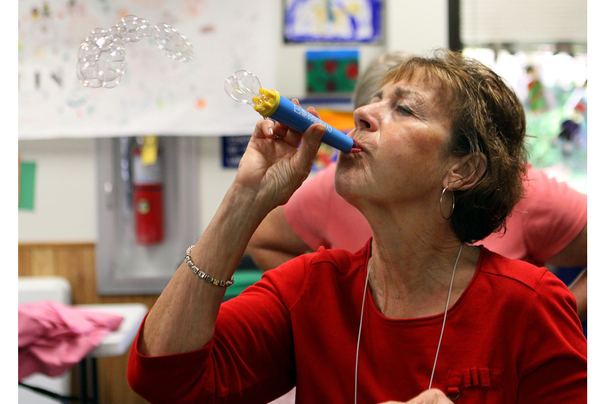 Janice Frankel blows bubbles as the children, parents and caregivers clean up the toys that were used during playtime.