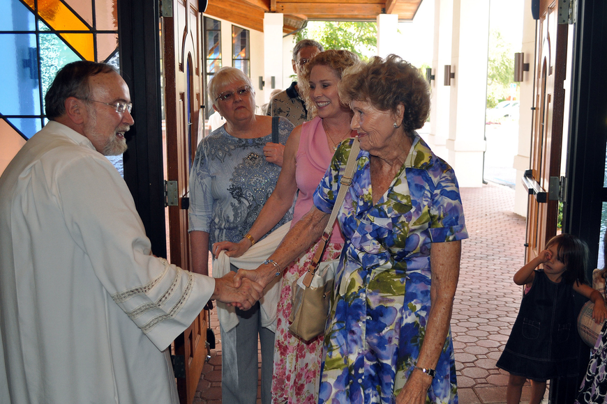 Anne Angers congratulates Msgr. Joseph Stearns on his 40th anniversary.