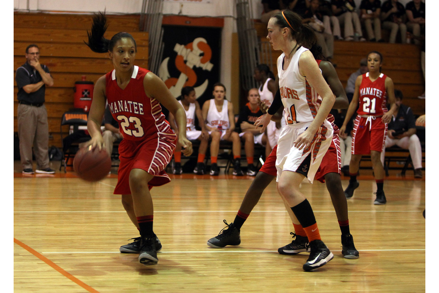 Manatee's Jasmine Luther, No. 23, keeps control of the ball while Sarasota's Emily Harding, No. 11, stays close.