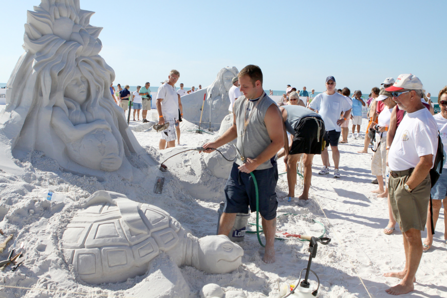 Sean Fitzpatrick sprays some water onto part of the sand sculpture