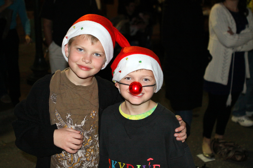 Elgin and Devin Lamperski enjoy watching the parade and wearing some Santa hats and a Rudolph nose.