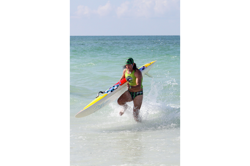 Sarasota County lifeguard Robert Martini runs hard through the water with his colorful board during the rescue board race.