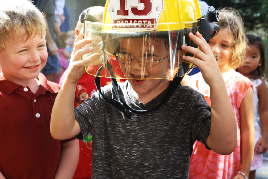 Logan Lutz watches as Chance McArtor can barely support the weight of a firefighter helmet.