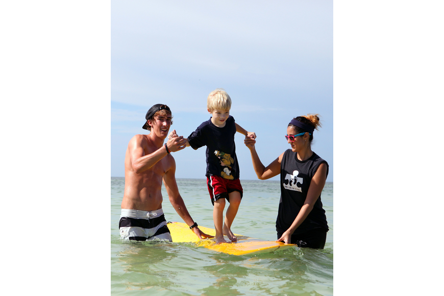 Keith Misja and Kate Maccarone help Drew Wojick, 5, ride on a surfboard Saturday, Sept. 15 during Hang 10 for Autism.