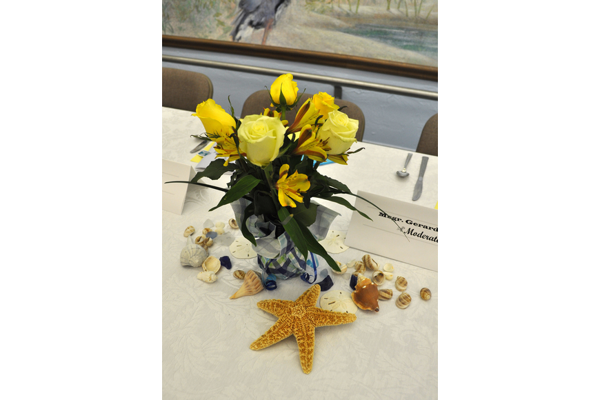 The tables were decorated with yellow roses in blue vases as well as a variety of seashells.