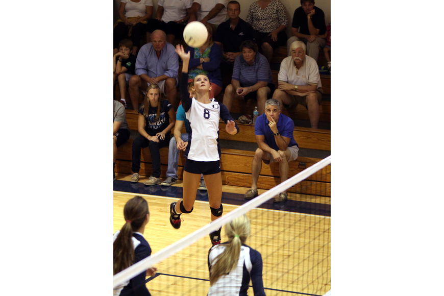 Lauren Maxey, No. 8, gets up high as she goes to spike the ball.