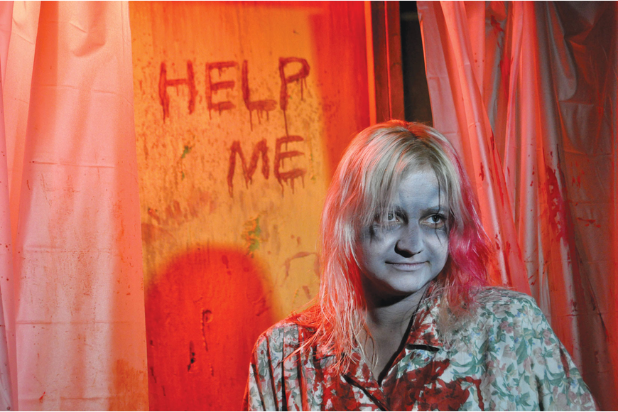 Shannon Braswell stands, soaked in blood, in a bathtub at the Frightmares Haunted House.