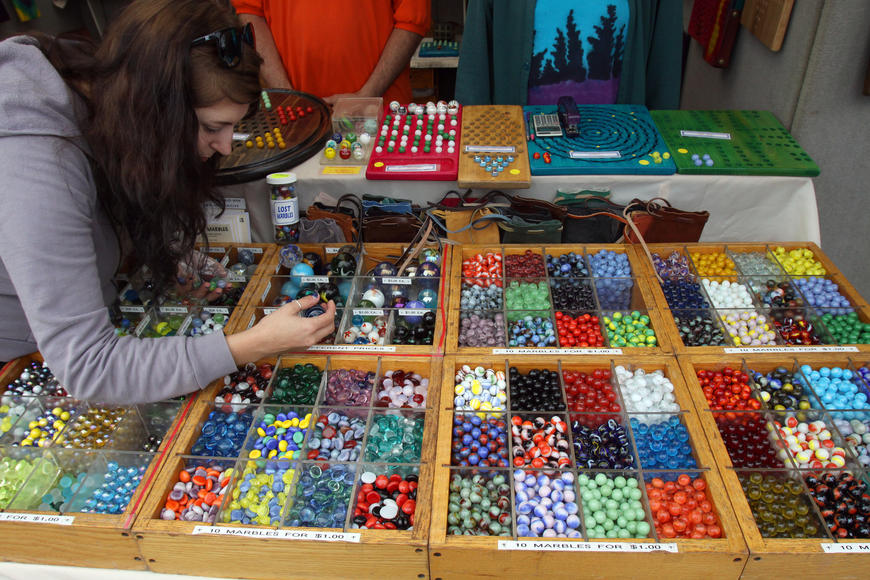 Jess Bolger searches for the perfect marbles to but from The Marble Guy at the 17th annual Siesta Key Craft Festival, Saturday, Feb. 5, in Siesta Key Village.