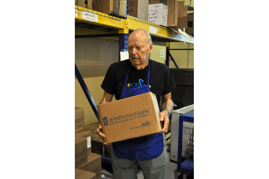 Bob Hambrecht carries boxes of cans that have already been packed at All Faiths Food Bank. Hambrecht and his wife, Carol, have been volunteering at All Faiths Food Bank for 14 years.