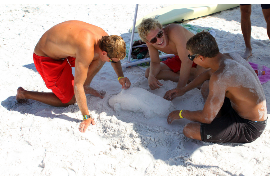 Brevard County lifeguards Robert Lenoci, George Pickett and Jon Ortiz make a race car out of sand during some downtime Thursday, July 14 during the 2011 James