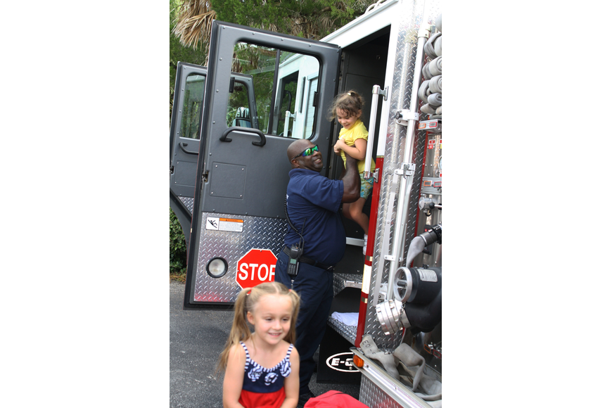 Violet Walsh Grins after taking a tour of the inside of the firetruck. Firefighter Ricky James hoists Giovanna Hansen out of the truck.