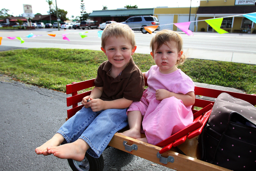 Caleb, 3, and Jerusha, 1 ½, Yoder sit in their little red wagon.