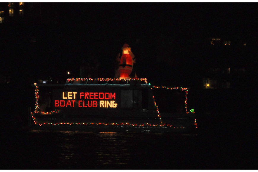 "An inflatable Santa was placed on the top of this boat that read ""Let Freedom Boat Club Ring""."