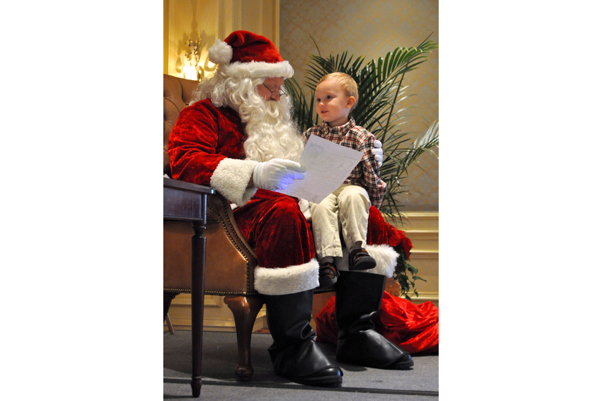Santa and Charlie Meyer, 2, go over the things Charlie wants for Christmas.