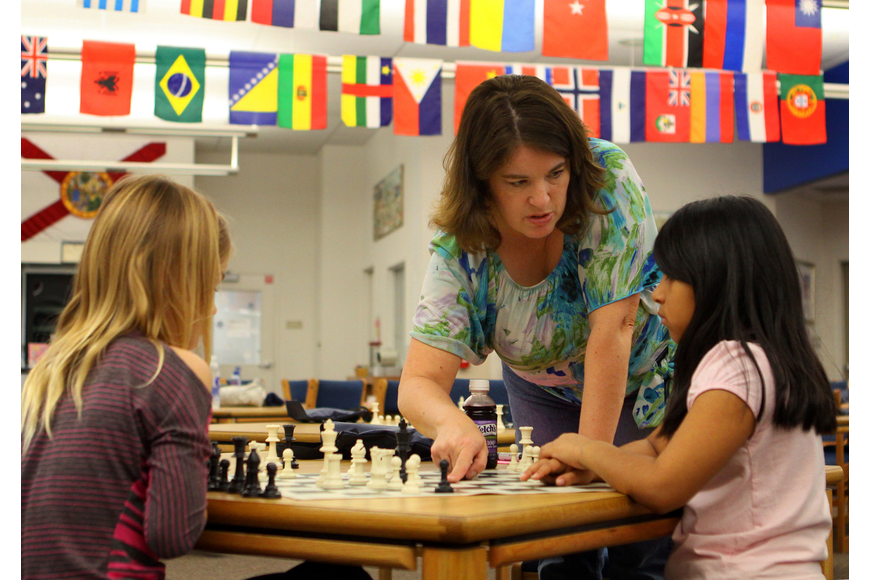 Pamela Doty, 3rd grade teacher and chess club advisor, helps Morgan Smith and Vanessa Aparicio, Saturday, Feb. 11, in the library at Phillippi Shores Elementary.