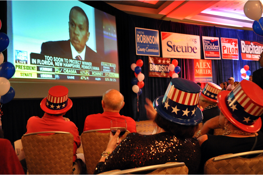 People watch election coverage on a giant screen during the election night party at the Hyatt.