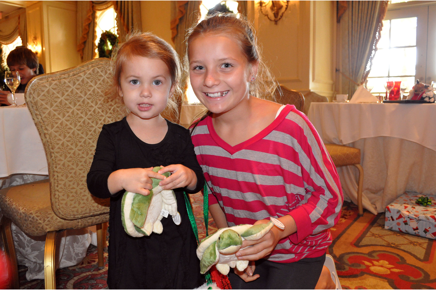 Samantha Chessler, 2, and Lexy Melone, 11, show off the stuffed animal turtles they received from Santa Sunday, Dec. 16, at the Breakfast with Santa event at the Ritz Carlton.