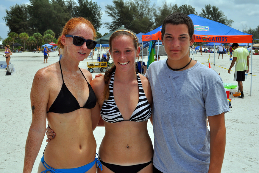 Volleyball teammates Stacy Werse and Melissa Perkins pose with their friend, Victor Davis, Saturday, July 9 at Siesta Key Beach.