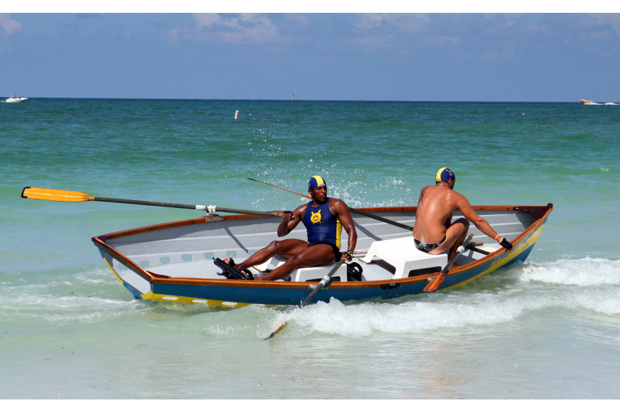 Hollywood, FL lifeguard Jose Luis Bolivar tries to keep the boat steady as his partner, Boki Corsovic, gets settled back in the dory during doubles surfboat competition.